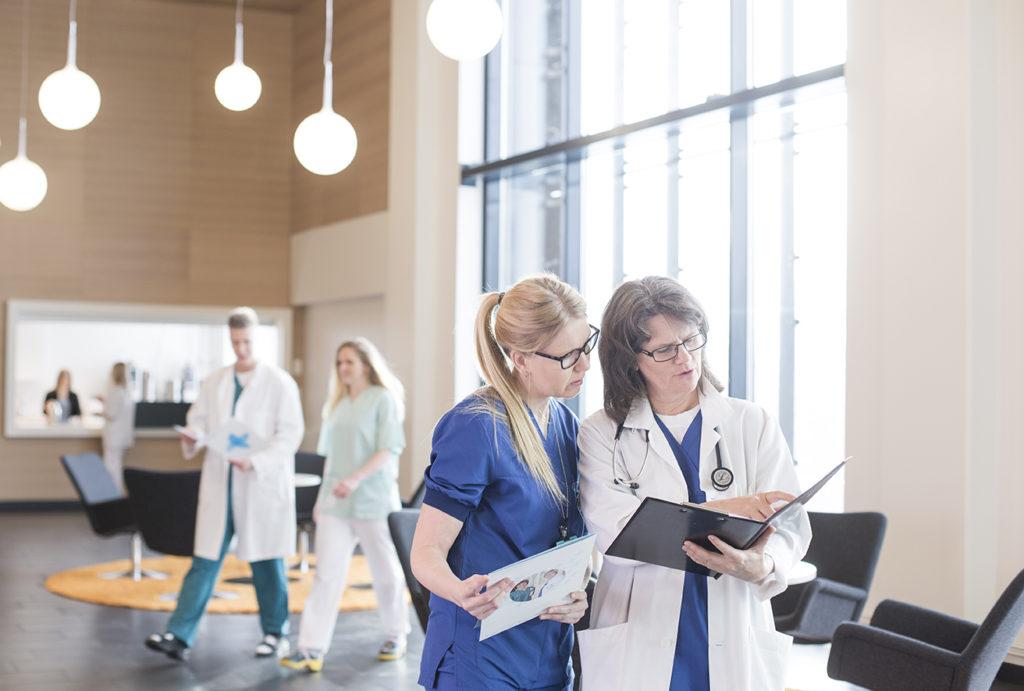 lääkäri ja hoitajat tutkivat potilaan tietoja