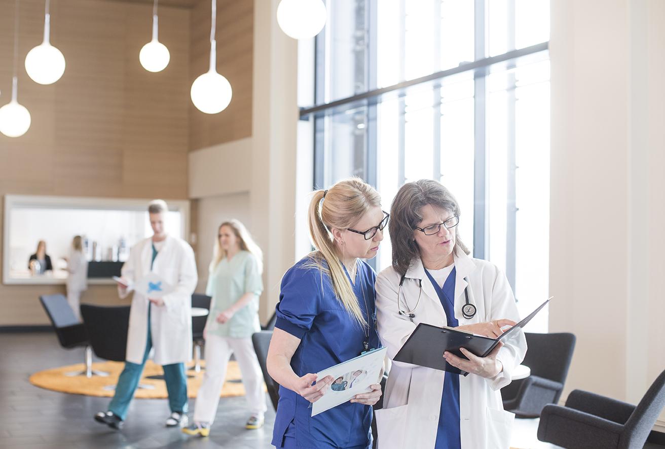 läkare och skötare tittar tillsammans på en journal