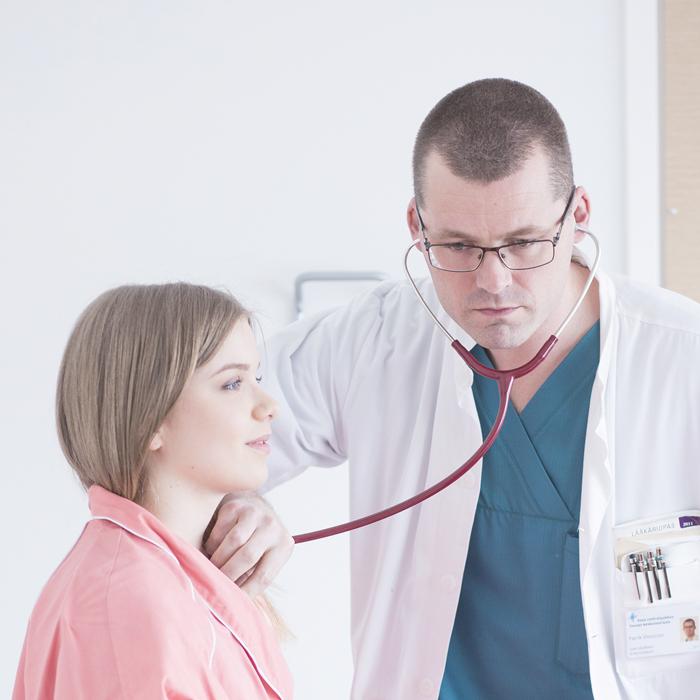 Läkare undersöker patienten med stetoskop