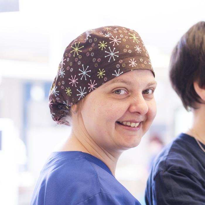 En kvinnlig anställd med en operationsmössa på huvudet